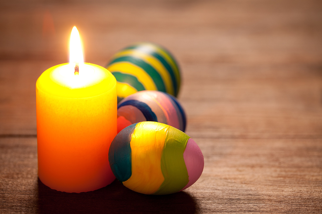 Colorful easter eggs and candle on old wooden table