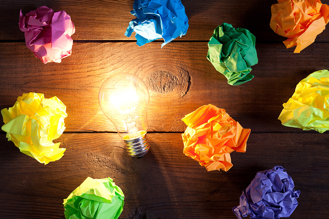 Incandescent bulb and colorful notes on old wooden table