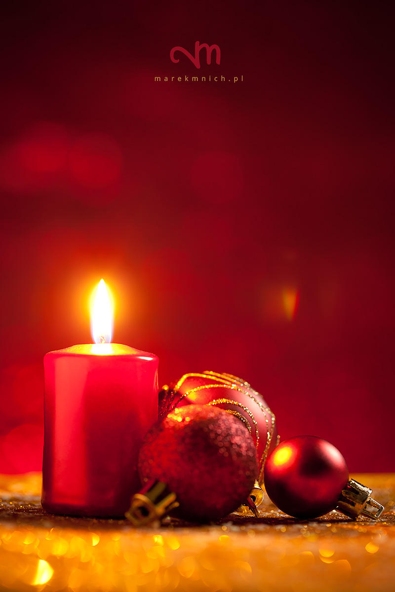 Candle and baubles on glitter with red background
