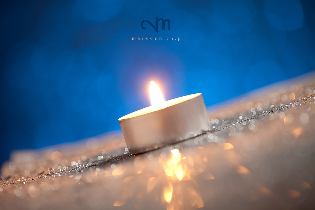 Candle on silver glitter with dark blue background