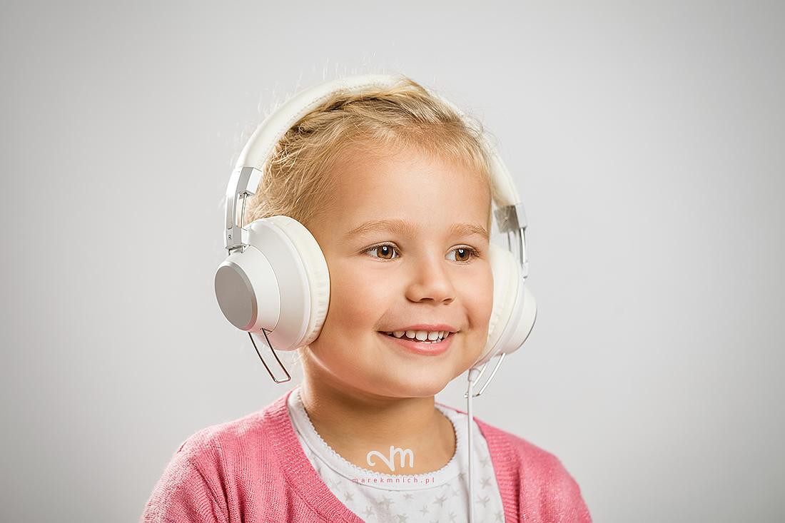 Cute little girl listening music on headphones
