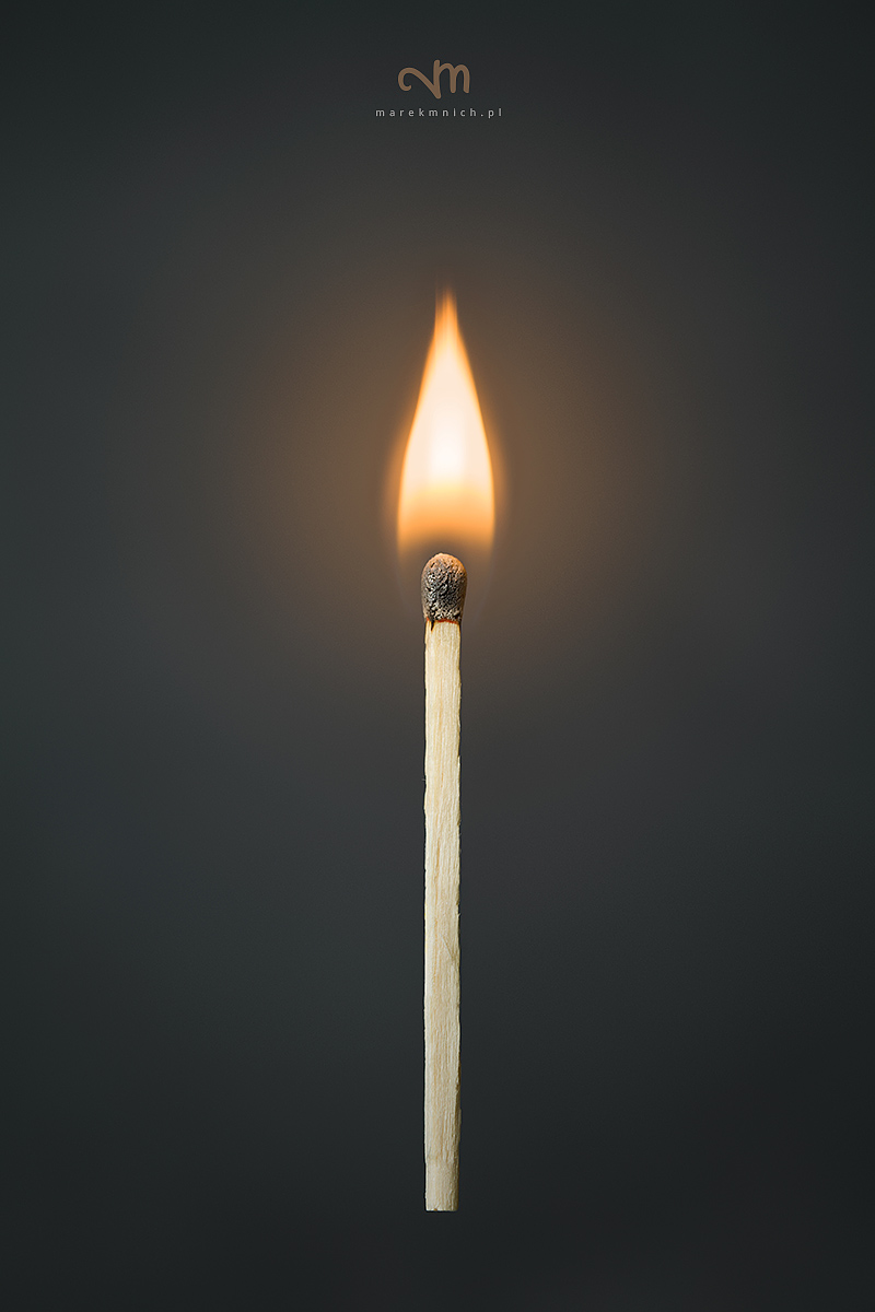 Burning match on dark grey background