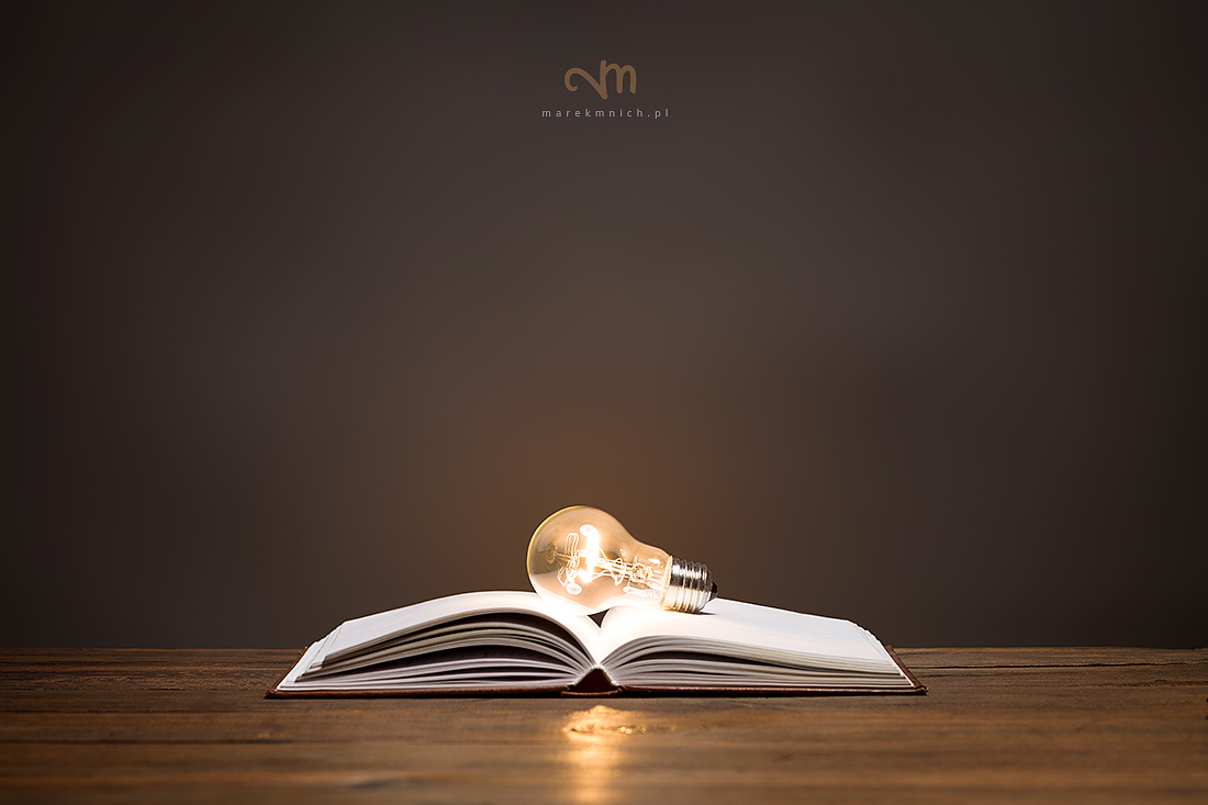 Incandescent bulb on open book