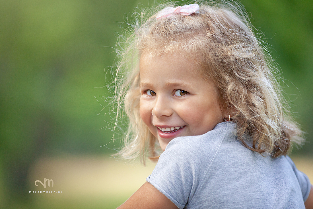 Smiling cute little girl on green background
