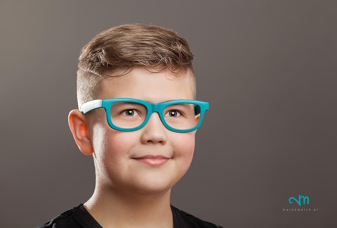 Teenager boy with eyeglasses on grey background