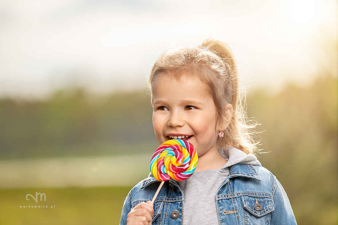 Smiling little girl with lollipop
