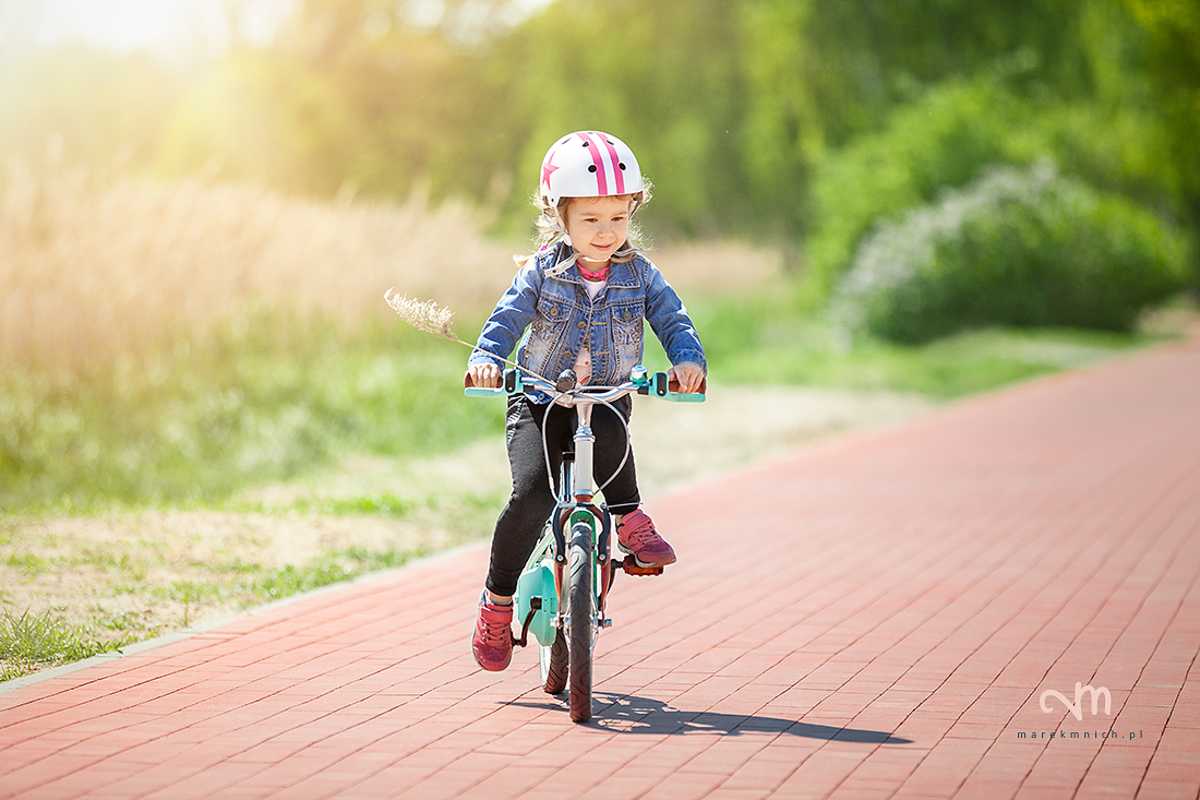 Cure little girl riding on bicycle